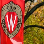 """A view of a """"W"""" crest banner with changing autumn leaves in the background."""