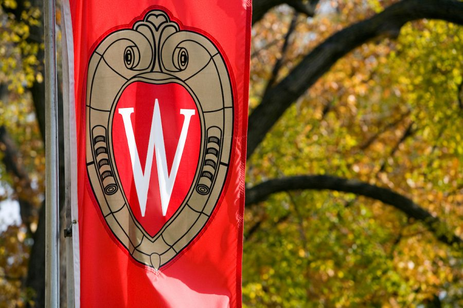 "A view of a ""W"" crest banner with changing autumn leaves in the background."