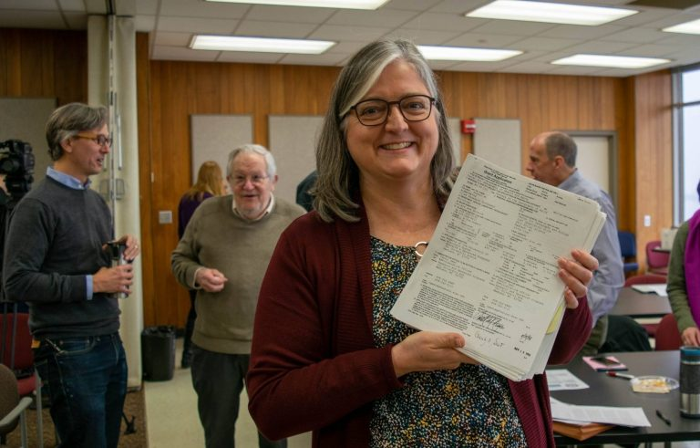 SSRS Director Janet Clear holding original grant submission she helped prepare in 1999.