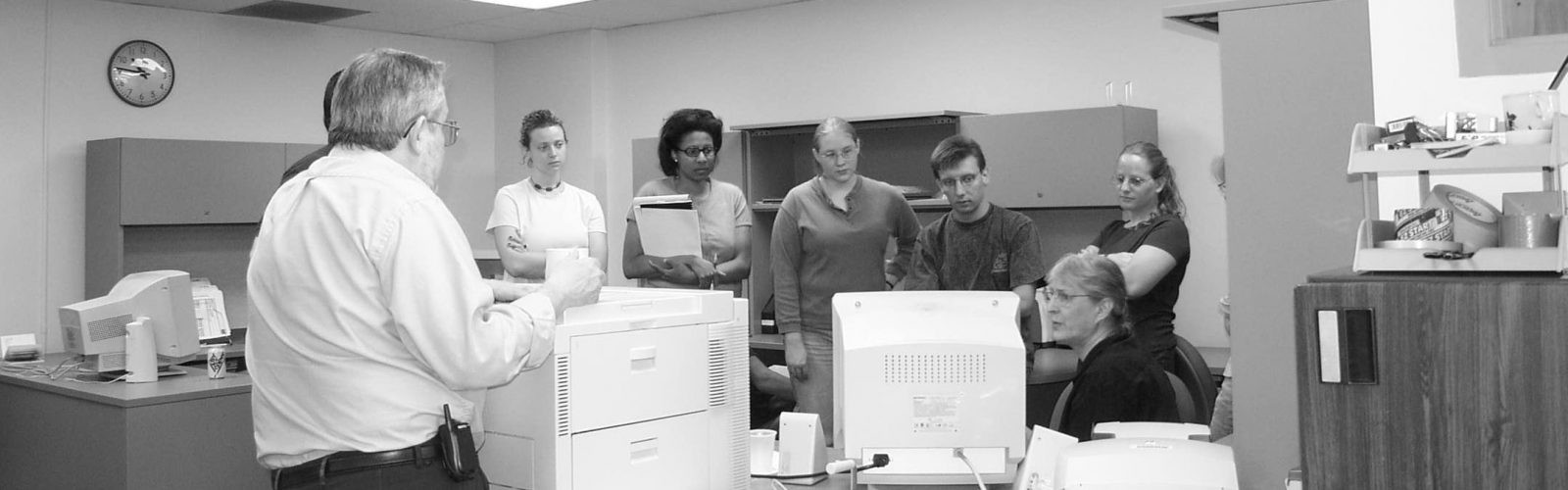 Black and white picture of researches talking in the office from the 60s.